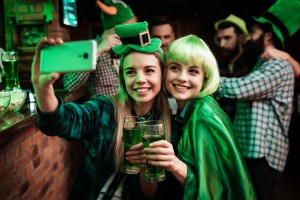 Two girls in a wig and hat make selfi at the bar. They celebrate St. Patrick's Day. They are having fun.