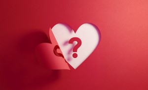 Question mark inside of a red folding heart shape on white background. Horizontal composition with  copy space. Uncertainty concept.